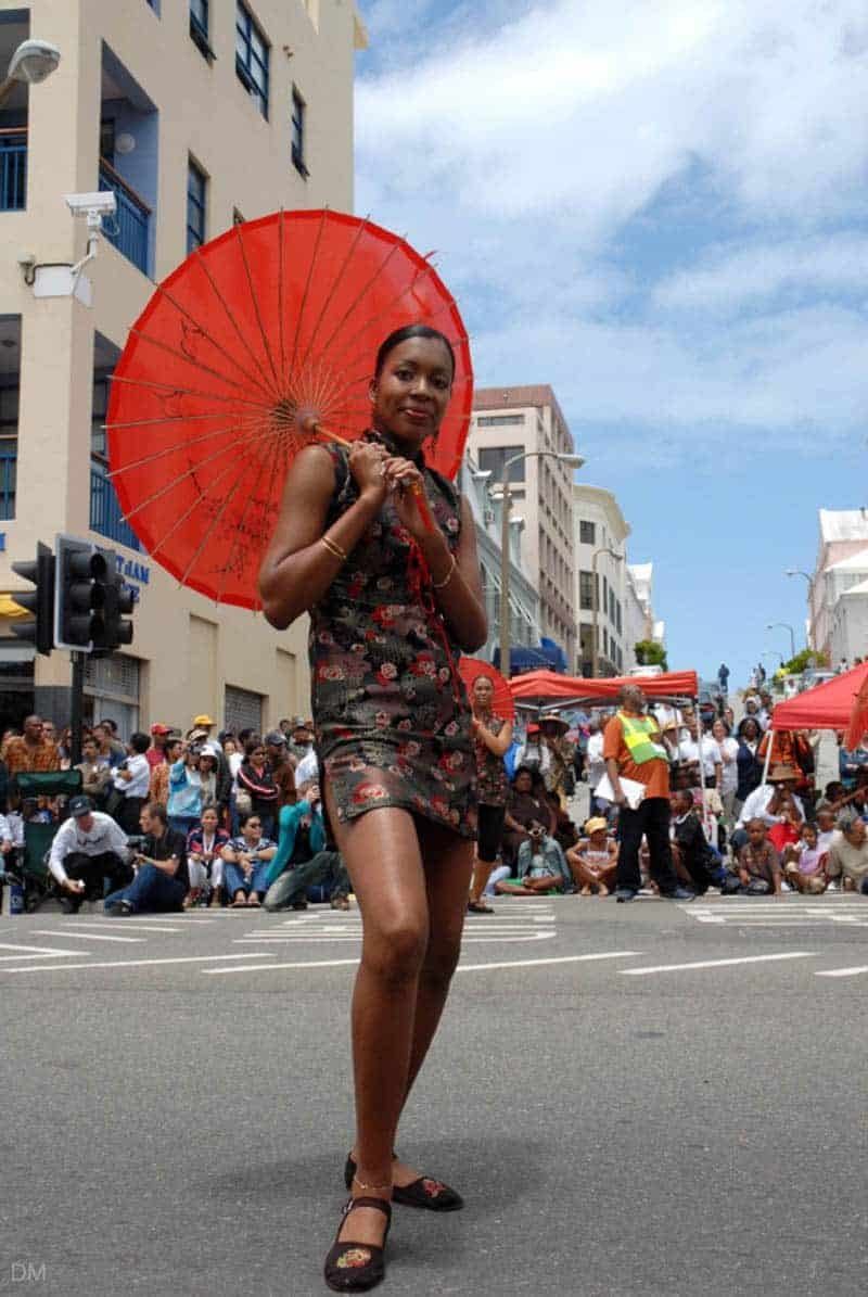Woman holding a red umbrella at the Bermuda Day celebrations in Hamilton