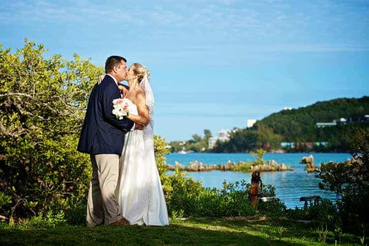 Bride and groom kissing with Castle Harbour in the background