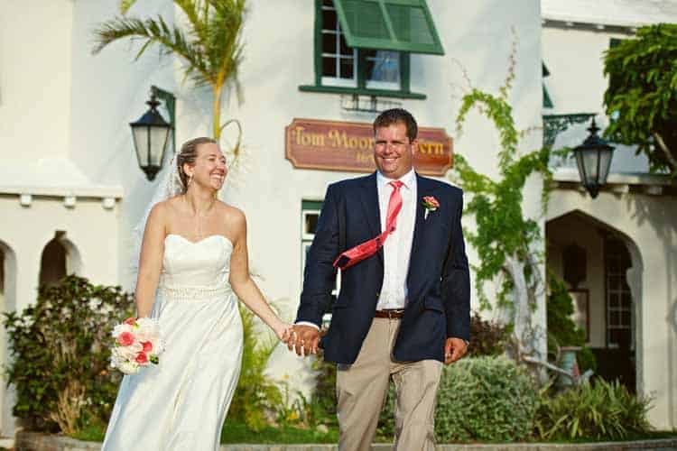 Bride and groom walking hand in hand outside Tom Moore's Tavern