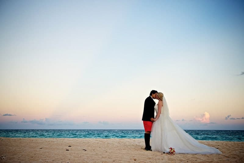 Bride and groom kissing on the beach at Rosewood Bermuda