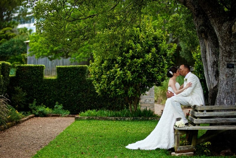Bride and groom kissing under a tree in the Bermuda Botanical Gardens