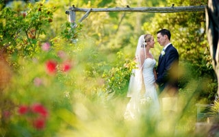 Bride and groom sharing a romantic moment in the gardens of Waterville