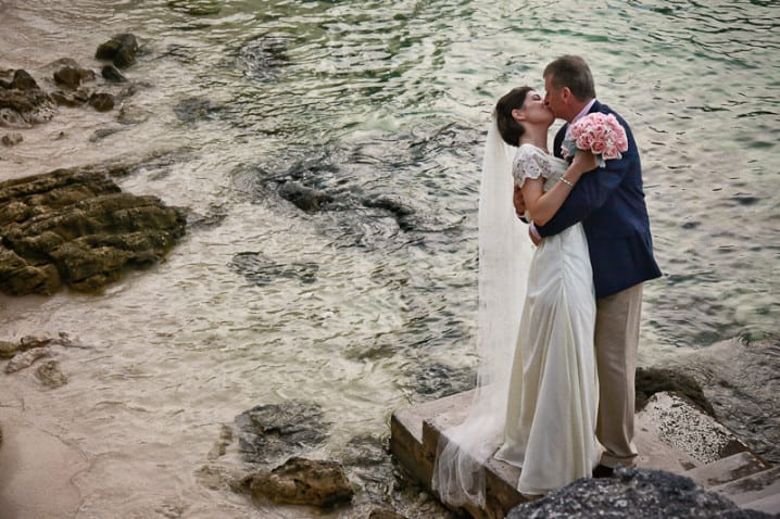 Newly married couple kissing on a beach in Bermuda by Bermuda wedding photographer Dee Storey