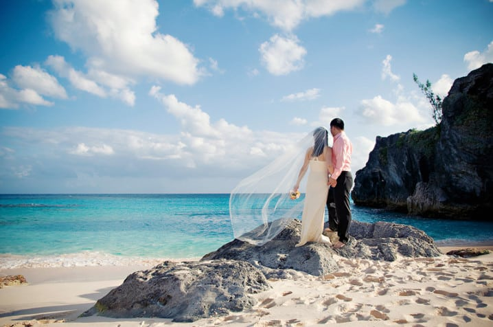 Bride and groom standing at Stonehole Bay in Bermuda and looking at the ocean